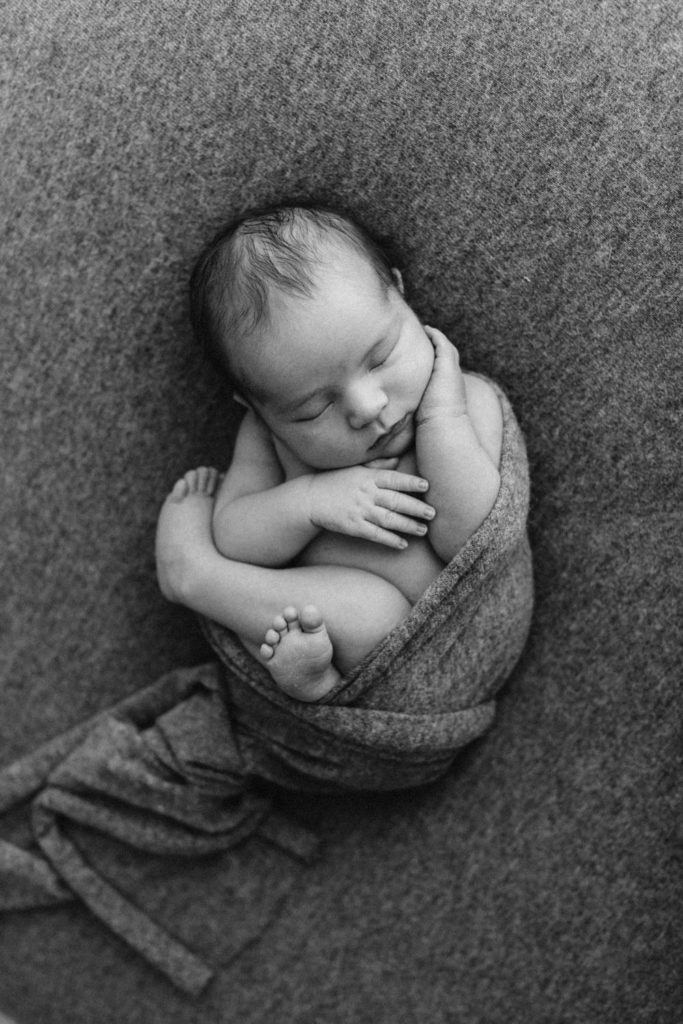 Sleeping newborn baby posing for photographer