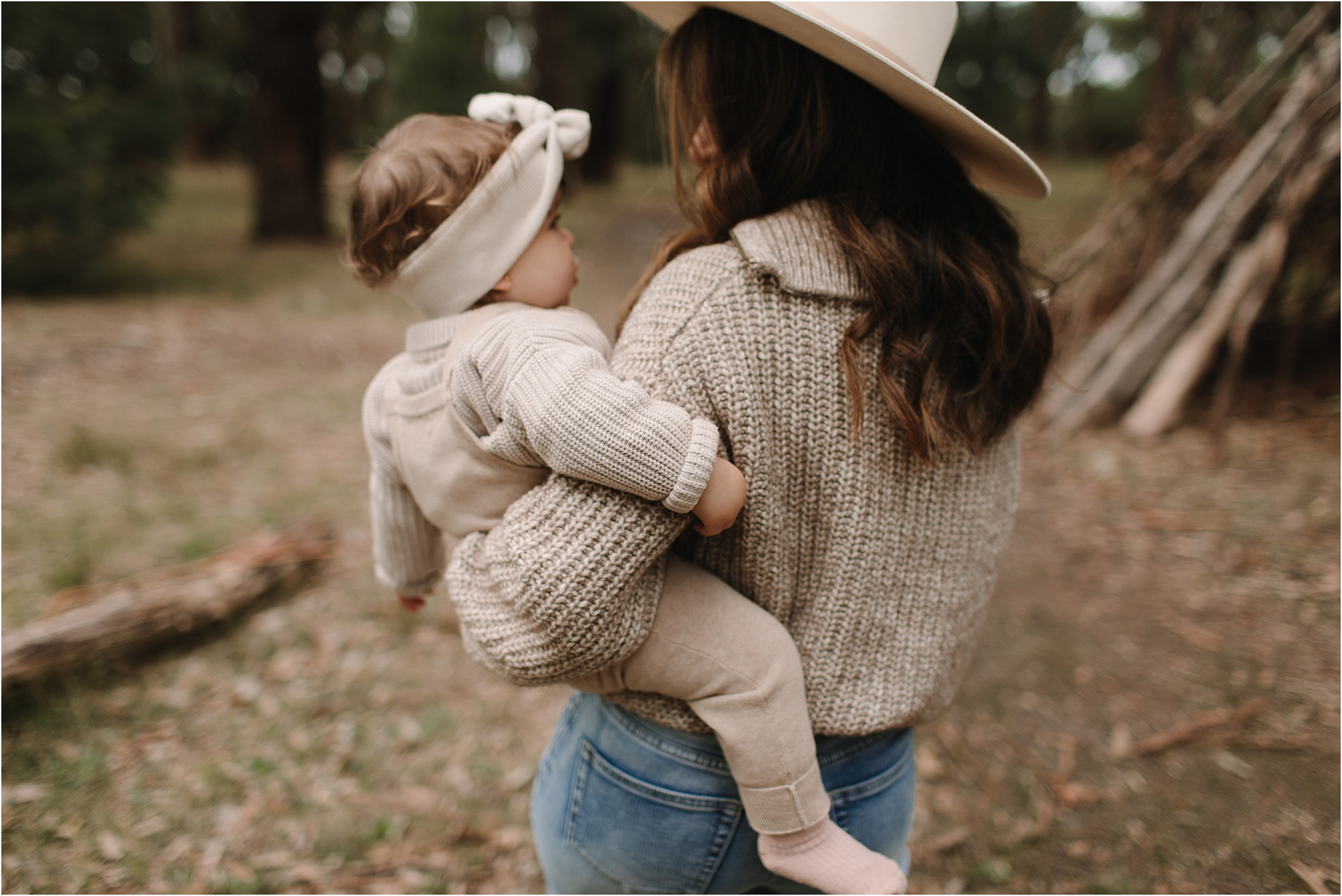 A portrait of Mum holding baby, walking away from the camera