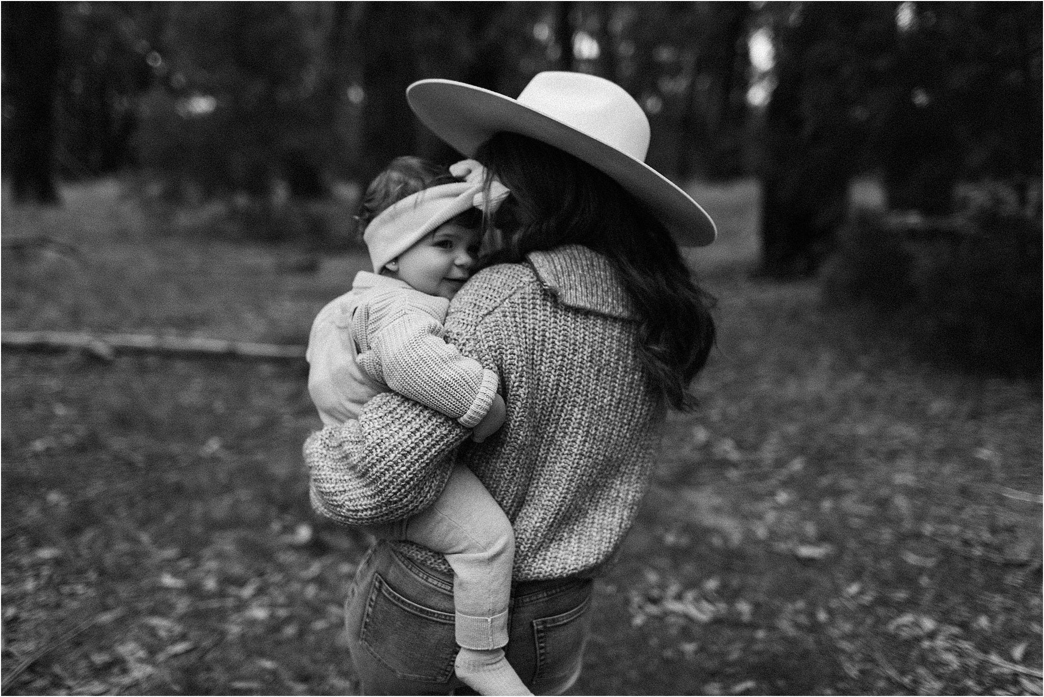 A black and white portrait of Mum holding baby, walsking away from the camera