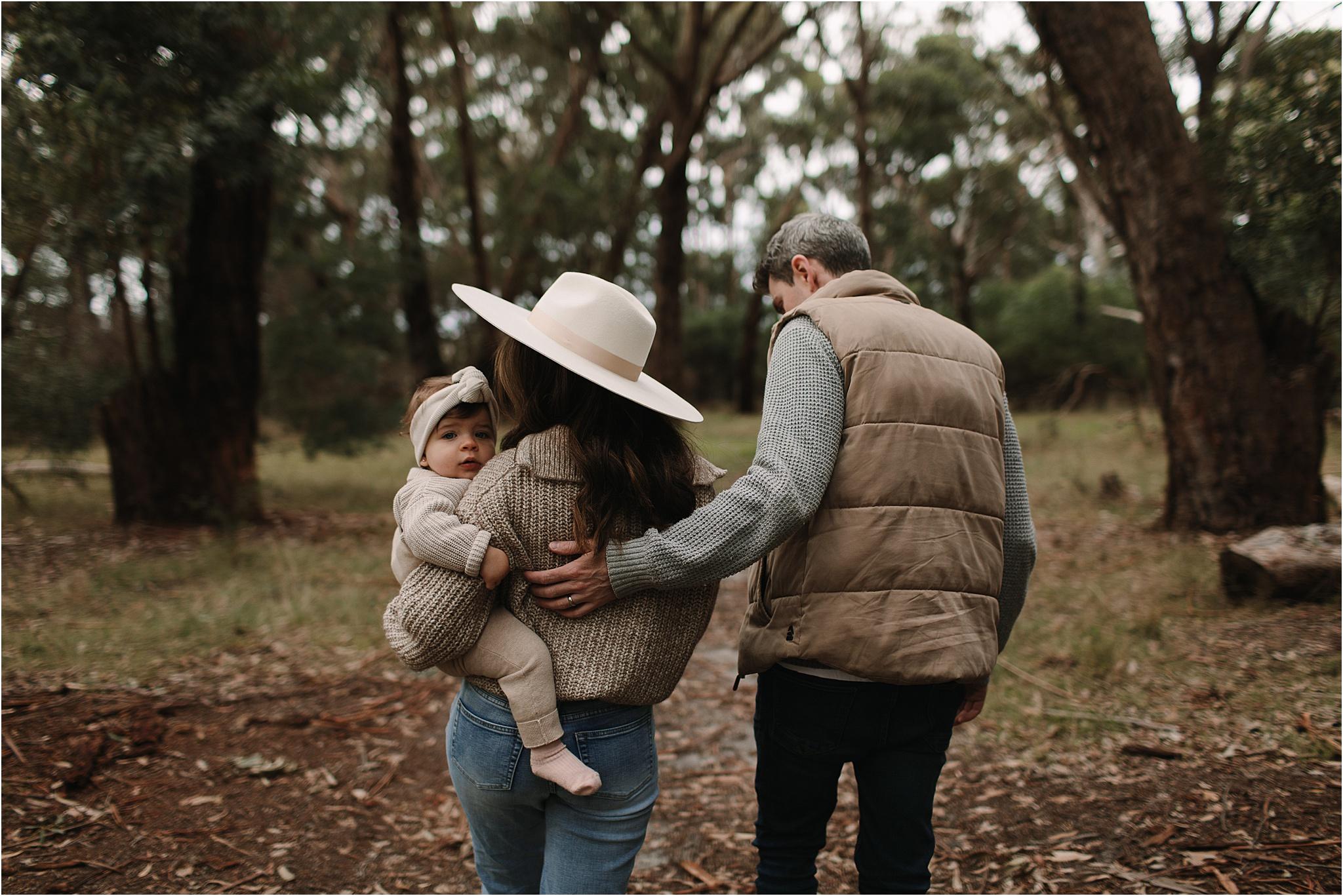 Mum, Dad and baby walking away, Dad holding onto mums back