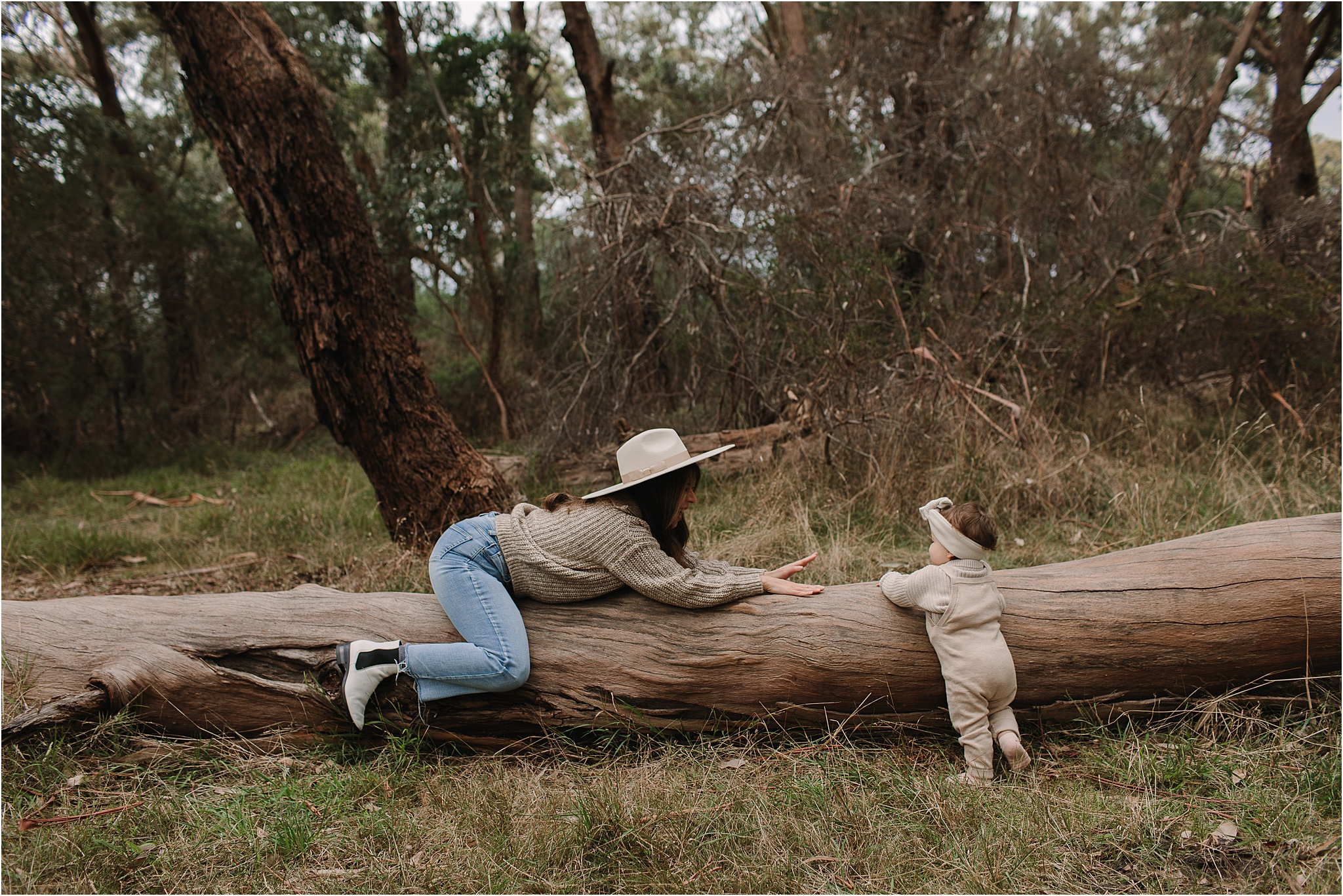 Mum having fun with toddler on a log in the bush
