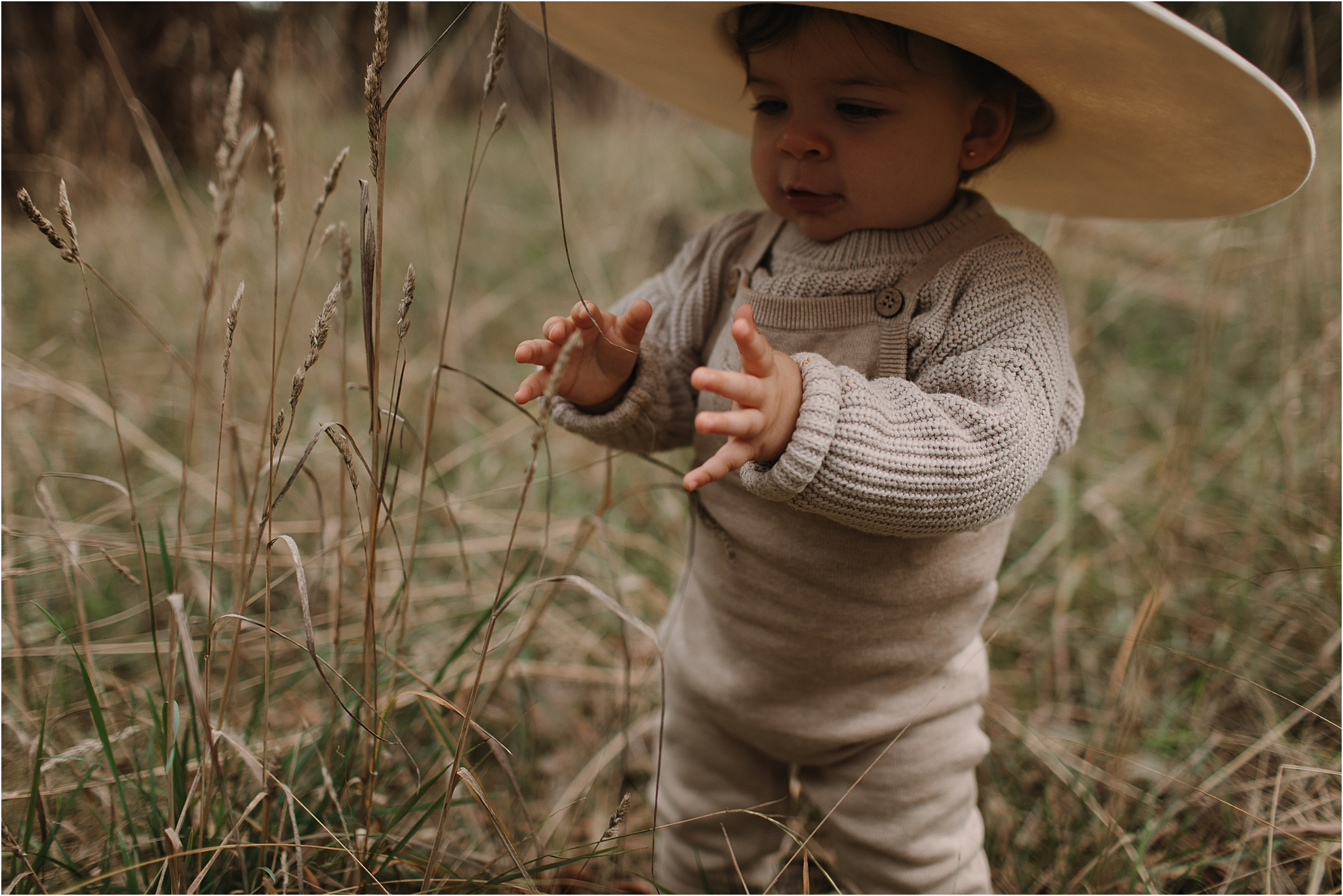 A toddler in a wide brim hat playing with long grass