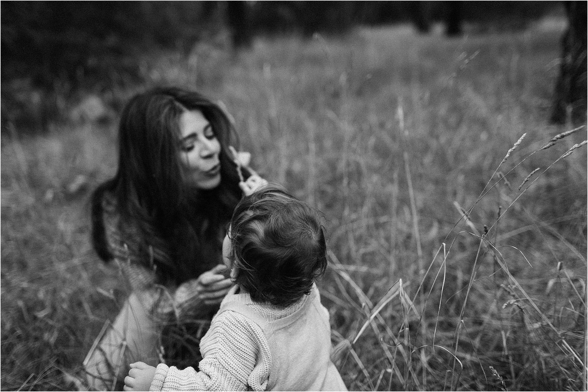 A black and white photograph of a toddler having mummy smell the grass