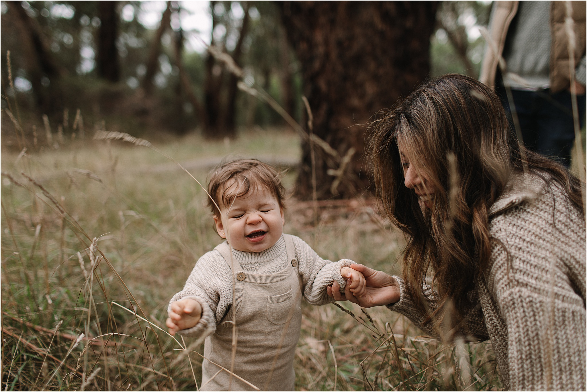 A funny expression on a toddlers face as the long grass tickles her