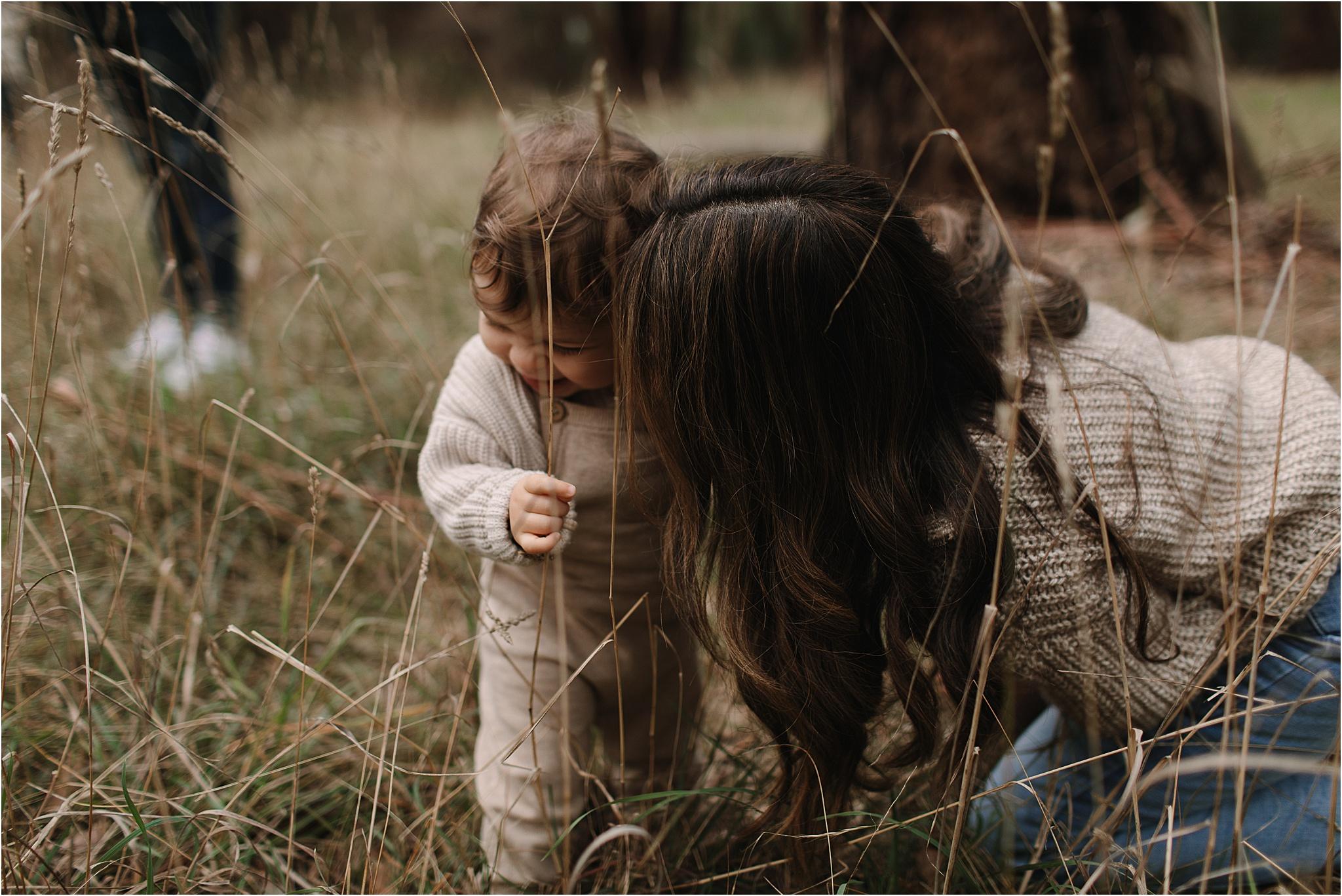 Mum kissing her toddler in long grass
