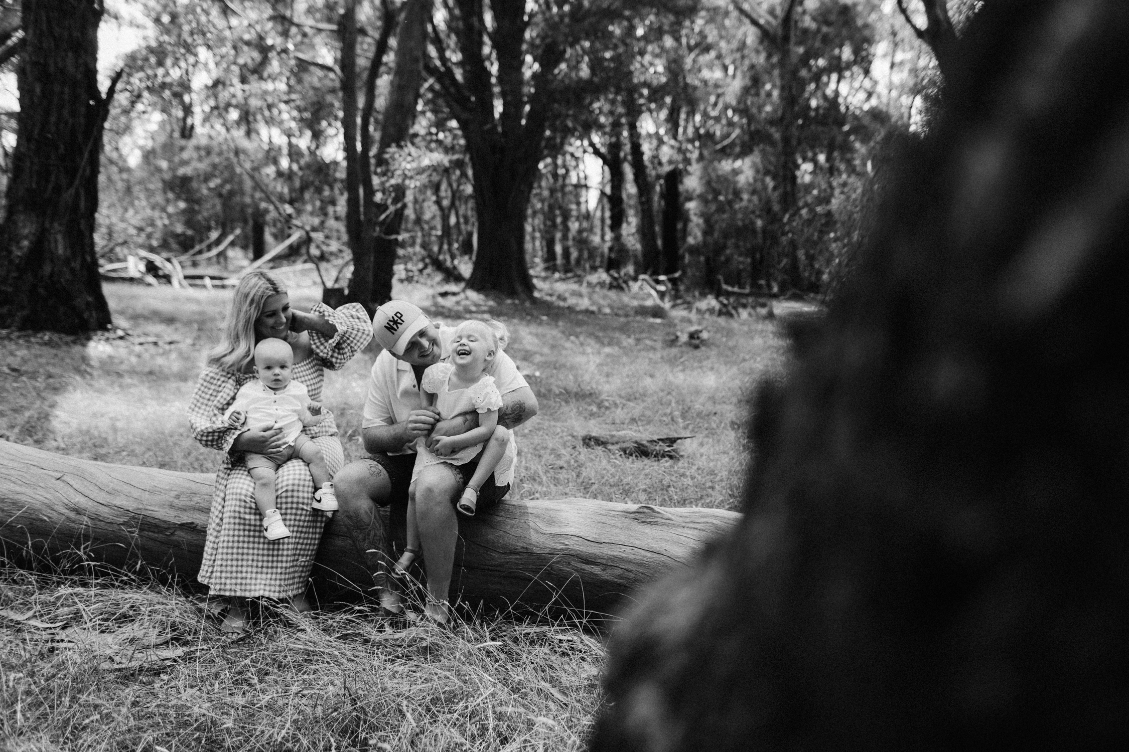 Black and white portrait of family sitting on a log